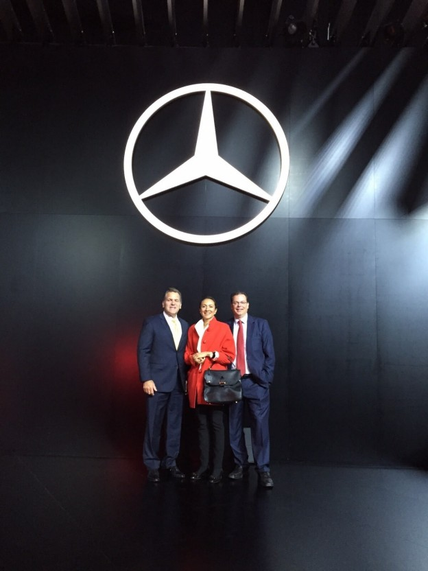 LIASE Group Managing Director for the Americas John Bukowicz (left), LIASE Group Managing Director Asia Vanessa Moriel (center) and LIASE Group President and Managing Director Europe Wolfgang Doell (right) standing in front of the Mercedes-Benz logo at the Frankfurt Motor Show.