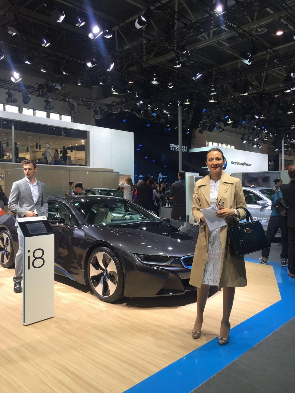 Liase Group's Vanessa Moriel poses in front of BMW's new open-top i8 Spyder Concept launched in Beijing. The new model is a convertible version of the i8 plug-in hybrid sports car.